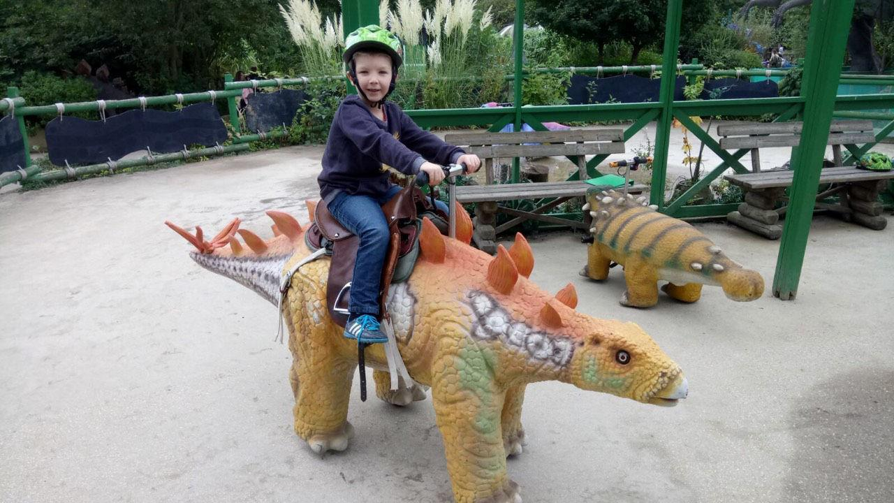 6 year old Zeke sitting on a dinosaur