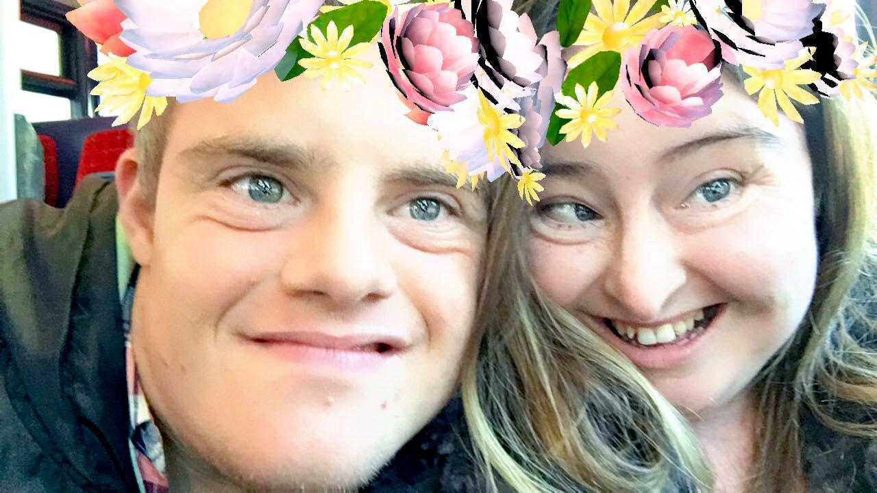 Hilly and Paul selfie with flowers in their hair from a phone app.