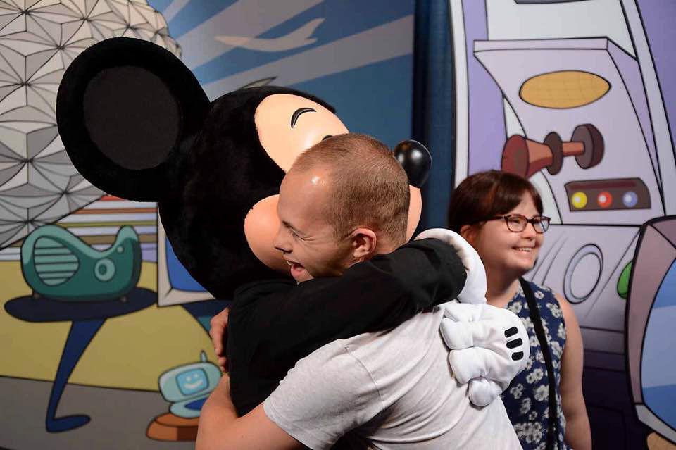 Sam hugging Mickey Mouse.