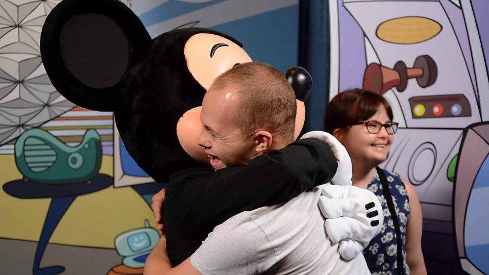 Sam hugging Mickey Mouse.