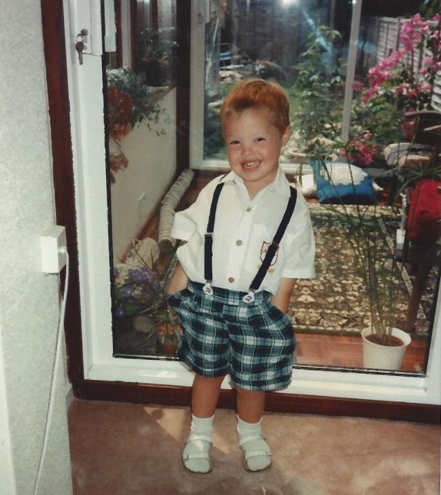 Sam as a toddler in checked shorts.