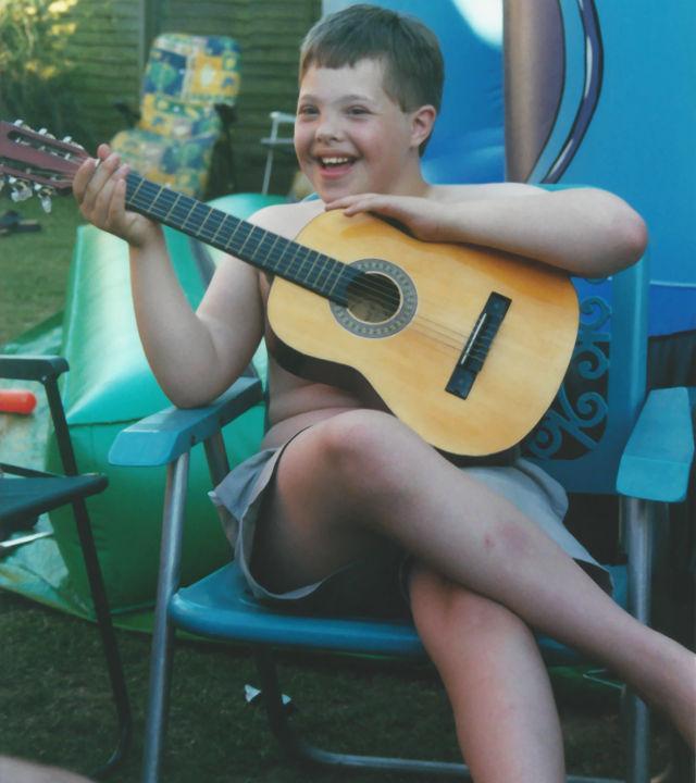 Sam holding a guitar.