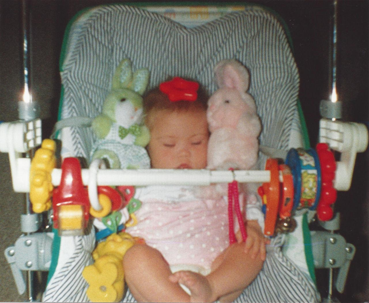 Megan as a baby with cuddly toys.