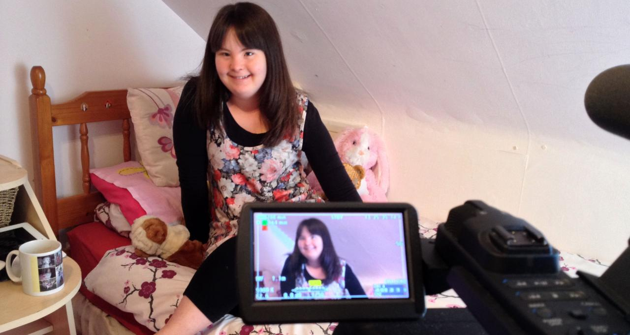 Megan being filmed giving an interview while sitting on her bed.