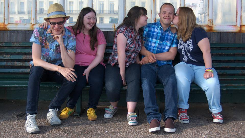 Lewis, Hilly, Megan, Sam and Lucy sitting on a bench on Brighton promanade. Lucy is kissing Sam on the cheek.
