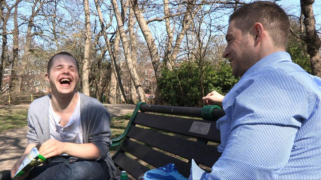 Sam laughing with Robbie on a park bench.