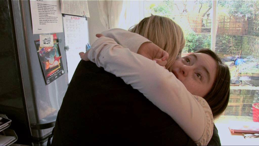 Hilly hugging her mum in the kitchen at home.