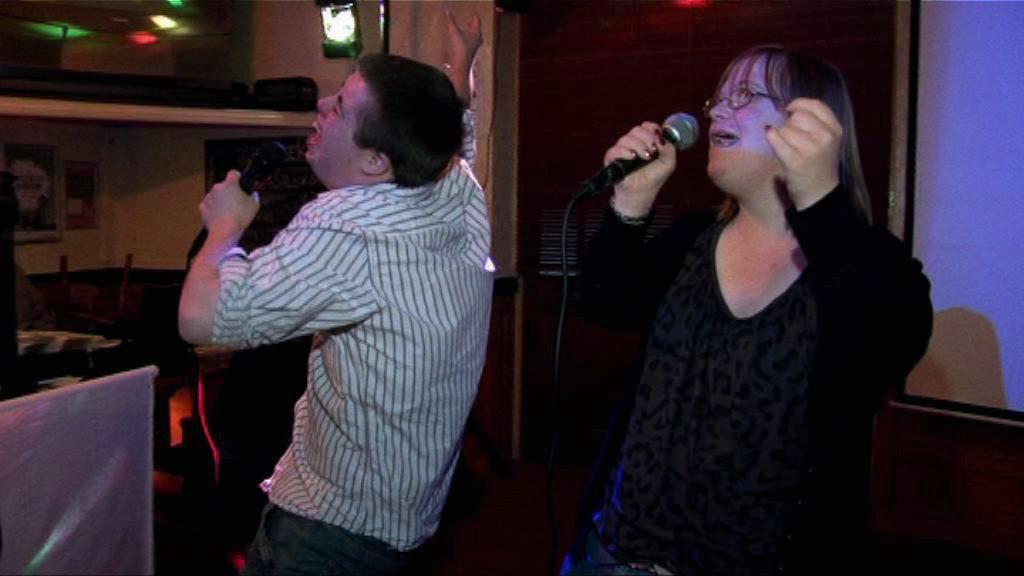 Nick and Lucy singing karaoke.