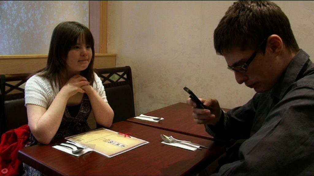 Megan and Lewis sitting at a table in a restaurant.