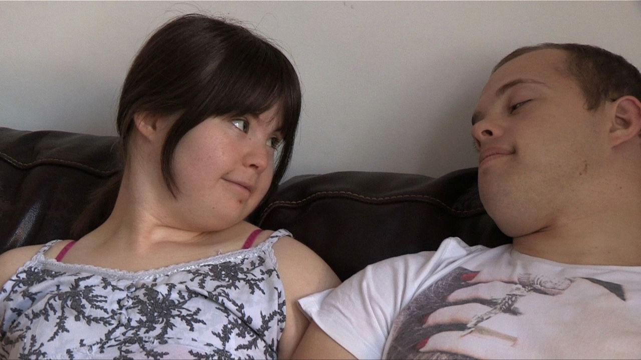 Megan looking questioningly at Sam on the sofa.