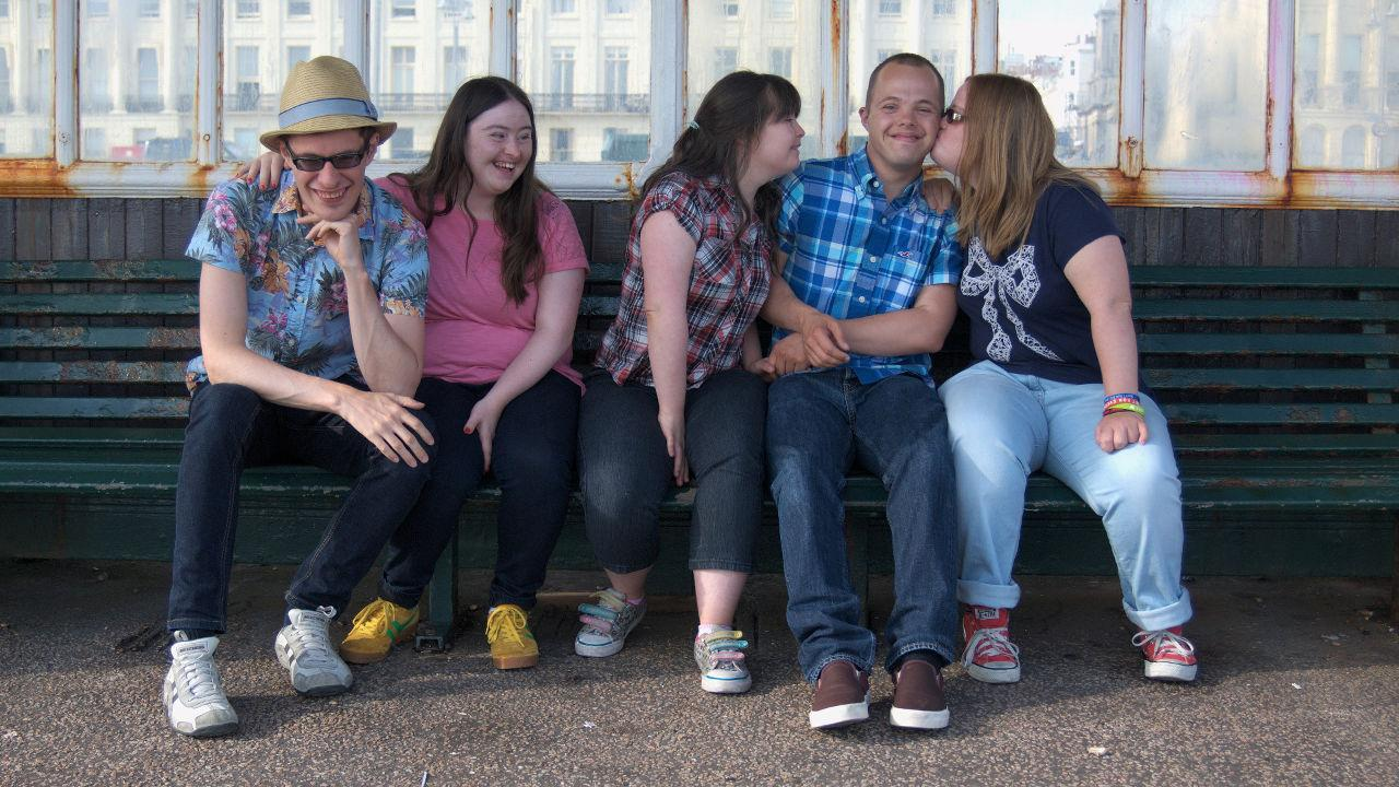 Lewis, Hilly, Megan, Sam and Lucy on a bench on Brighton promanade. Lucy is kissing Sam on the cheek.