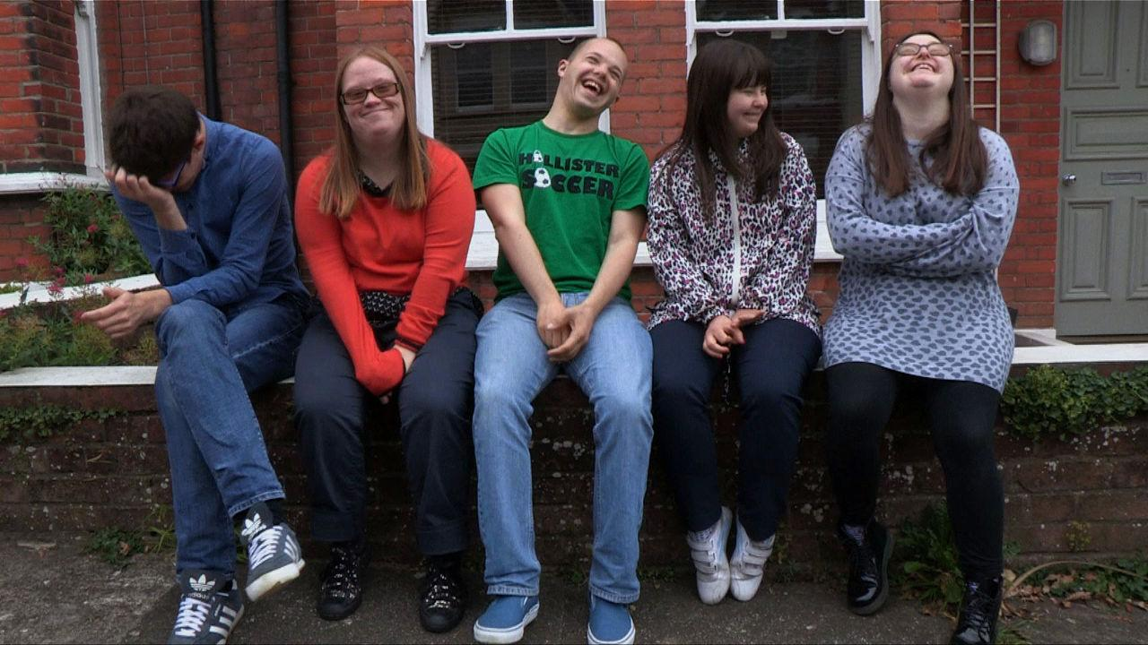 Lewis, Lucy, Sam, Megan and Hilly sitting on the wall outside their house.