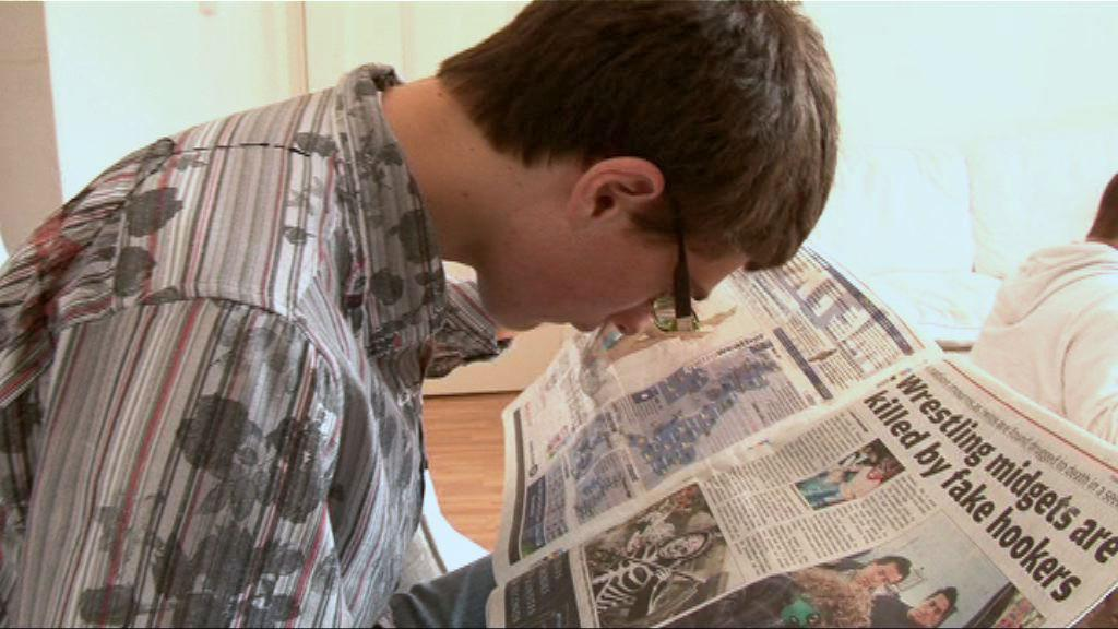 Lewis reading the newspaper