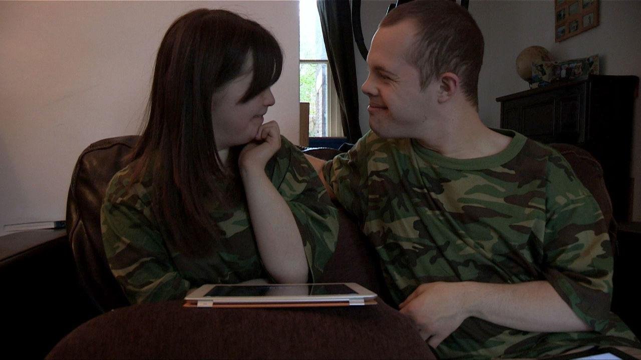 Megan and Sam looking at each other flirtatiously whilst wearing camo T-shirts.