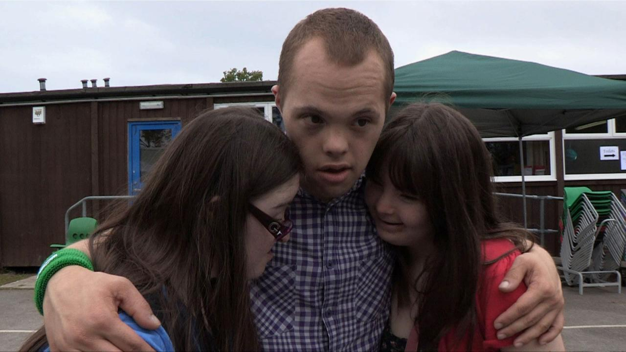 Hilly, Sam and Megan hug at their school reunion.
